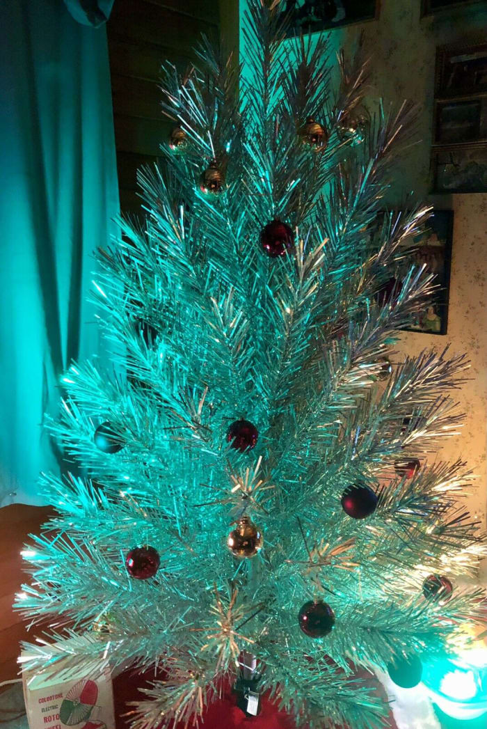 The 94-branch vintage 6-foot Evergleam lit up in teal, with the aid of a color wheel.