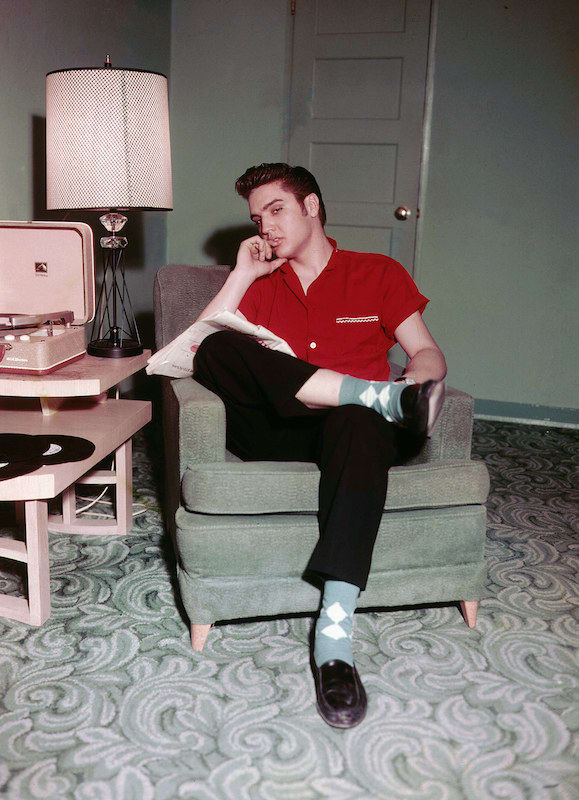Elvis looking casual and cool while relaxing at home in 1956. Dig those argyle socks and penny loafers – and the RCA Victor record player.