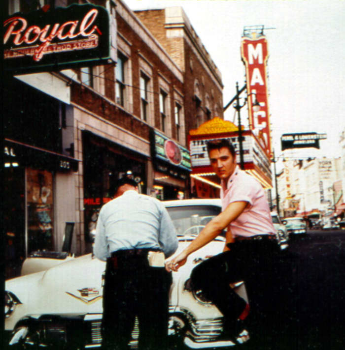Elvis even looks stylish while getting a parking ticket in Memphis in 1956 outside of Jim's Barber Shop. I love that he's wearing pink and that the red touches on his belt match his red socks.